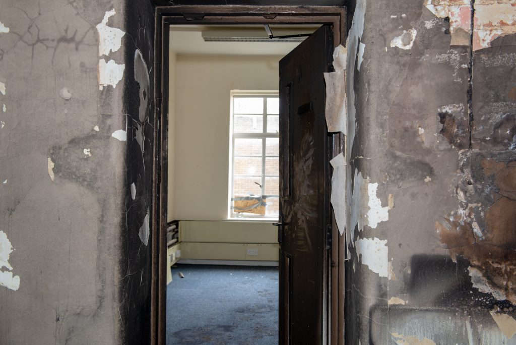 A fire door open at the museum, showing damage on one side and protected walls on the other