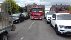 A crew in a fire engine attempting to drive down a street with heavy parking on either side