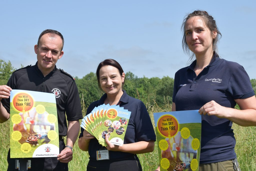 Steve Swan and Tina Collett from Northamptonshire Fire and Rescue Service photographed with Debbie Samwell, a parks ranger, launching the Summer Fire Safety Campaign