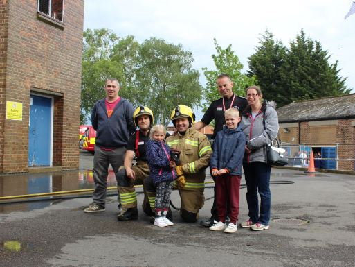 Family with firefighters at the fire station fun day held for families affected by Regent Street fire