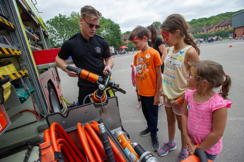 Firefighter shows some visiting children around the contents of a fire engine at last year's fun day
