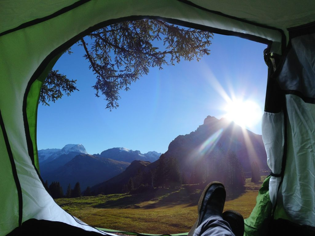 Feet extended out from a tent to mountain views