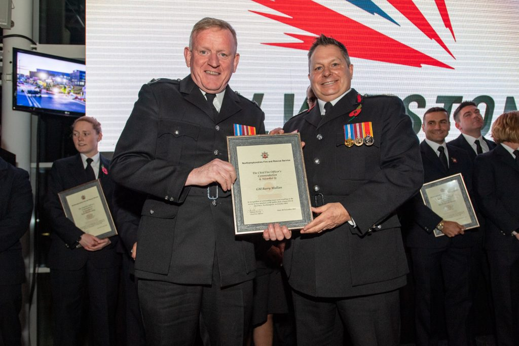 Group Manager Barry Mullan was among the group of Northamptonshire Fire and Rescue Service and East Midlands Ambulance Service staff commended for saving two people from a house fire in Northampton. Pictured with Chief Fire Officer Darren Dovey