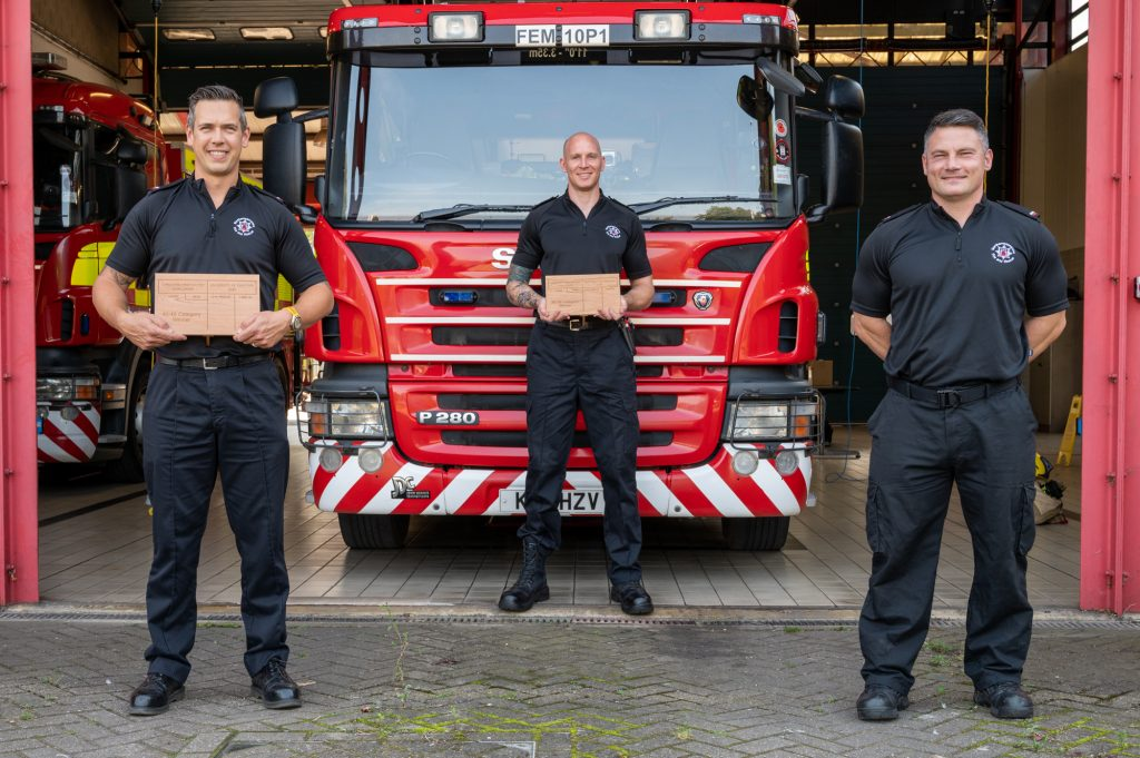 Pictured: Firefighters Dean Keeber, Aaron Childs and Paul Webb standing in front of a fire engine with trophies
