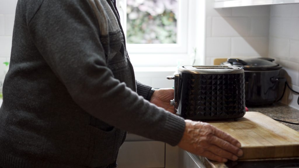 A person standing in a kitchen with toaster
