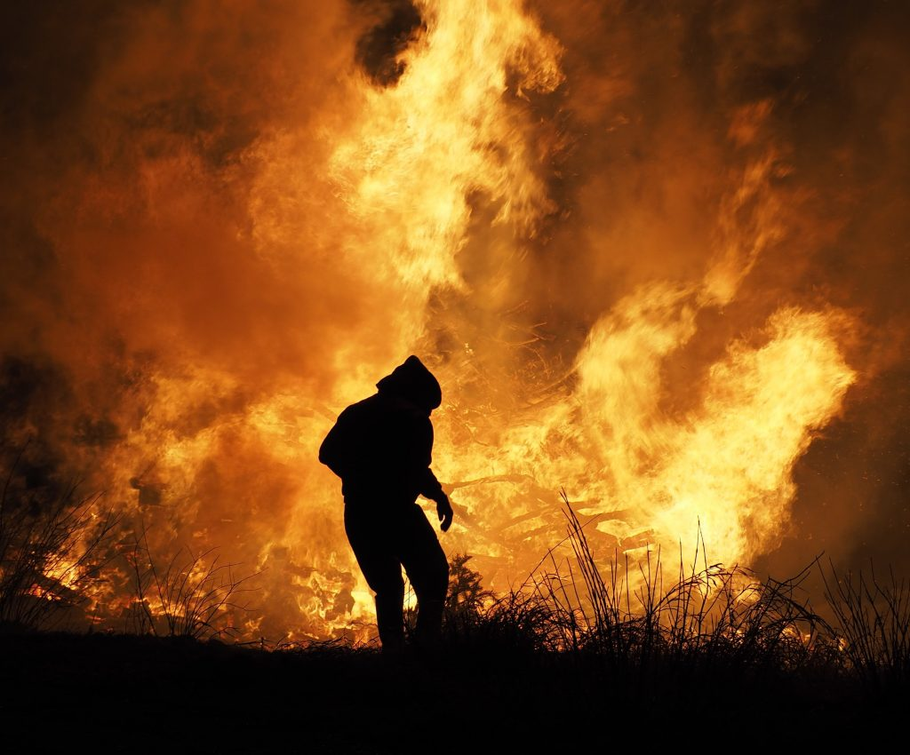 Silhouette of a person against a wildfire