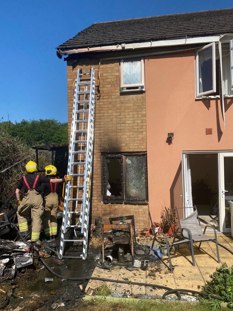 Image shows domestic property fro the outside. Badly damaged by fire, with 2 firefighters and a ladder