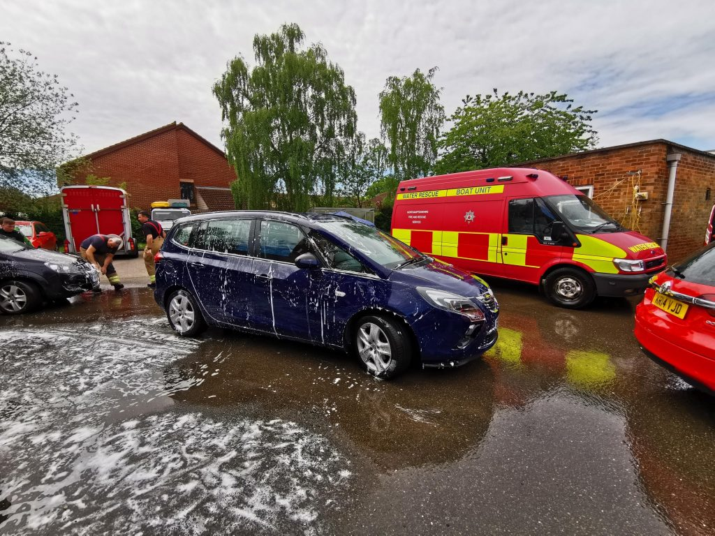 A soapy car being washed by firefighters