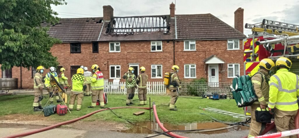 Image of house affected by fire with fire crew